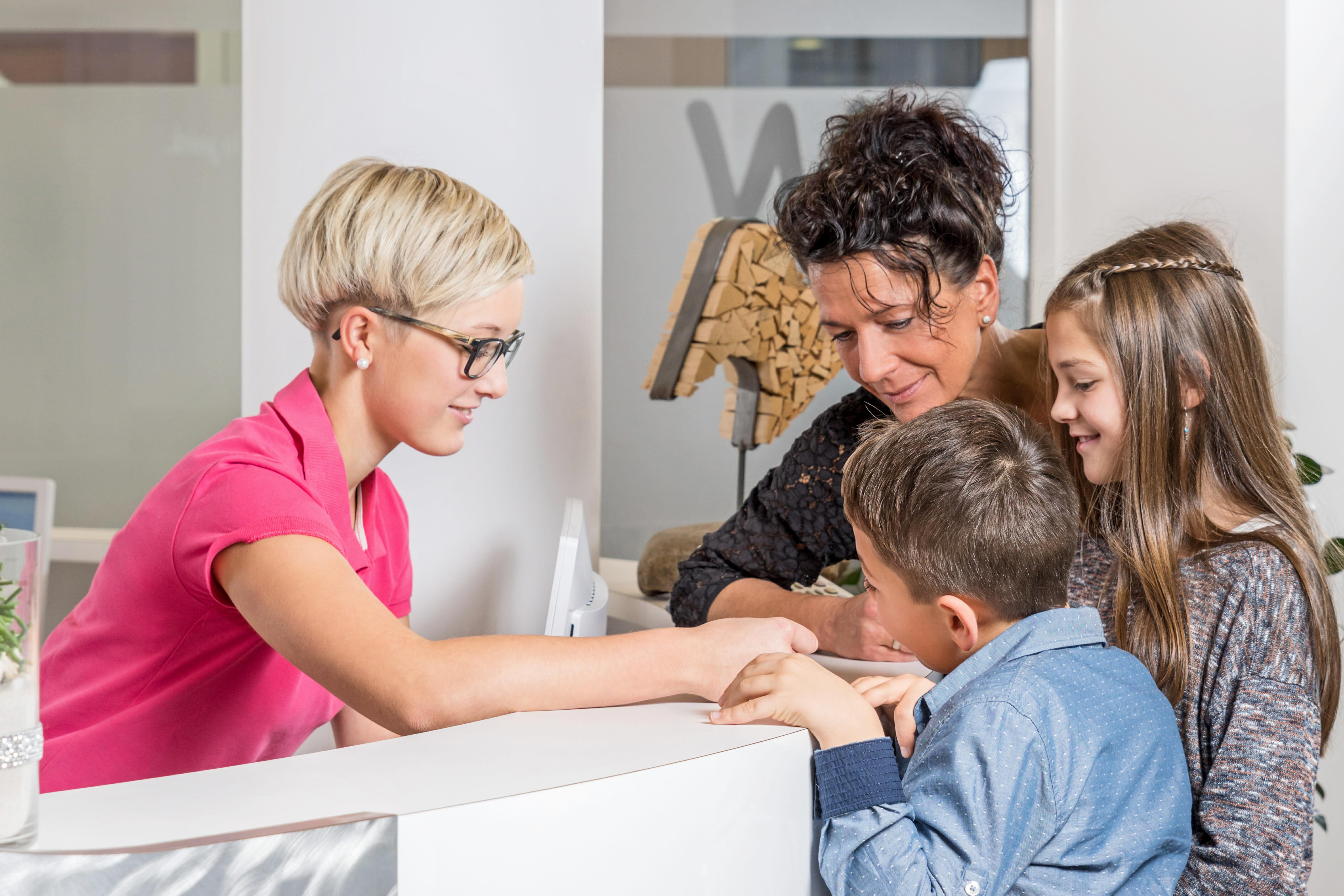 Junge Zahnarzthelferin schreibt einer Mutter mit Kindern Termin
